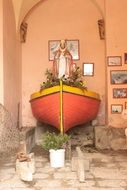 flowers and religious statue in a decorative boat on the island of Corsica, France