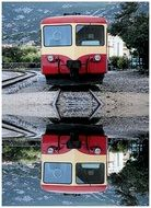 train and train reflection in a puddle