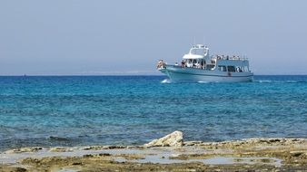 tourist yacht swims past the rocky coast in Cyprus