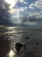 photo of the sun and thunderclouds over the evening beach