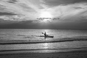 man on a boat kayak at sunset black white photo