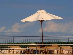 white umbrella over sun loungers on a sunny day