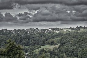 dark gray storm clouds over green forest