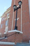 black street lamp in front of a brick building