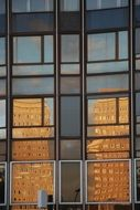 reflections in the windows of the facade of the building