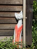 ceramic figure of a cat in front of a wooden house