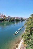 anchored boats on river in front of old city, switzerland, basel