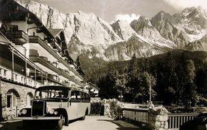 retro postcard with a car on the background of the top Zugspitze