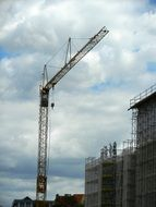 Construction crane and scaffolding in the background of a cloudy sky