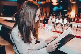 woman with brown long hair is studying the menu