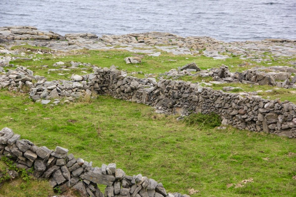 ancient stone wall green grass water ireland