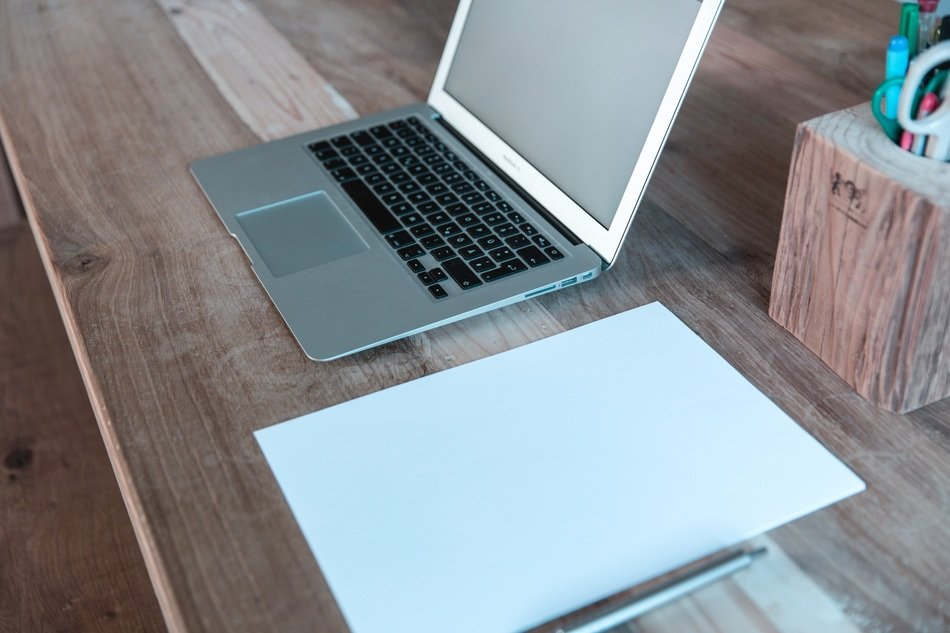 laptop and stationery on a wooden table