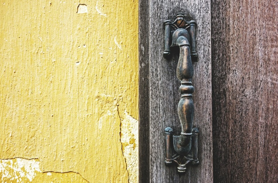 Old door handle on a wooden door