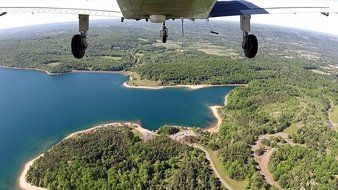 bottom view of plane in flight above scenic bay
