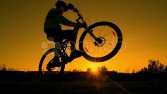 cyclist doing a stunt at sunset