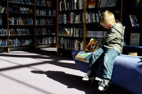 young boy sitting in library