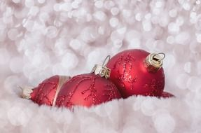 red Christmas baubles on a blurred white background