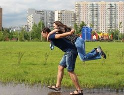Men is helping woman to cross the puddle