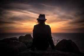 person in hat sitting seaside sunset