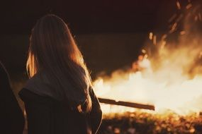 blonde woman looking at fire