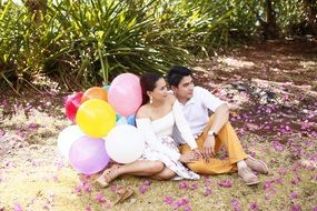 young couple with balloons sitting at ground