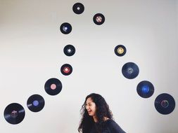young woman laughing on the background of vinyl records