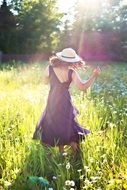 pretty woman dancing in sunny green field