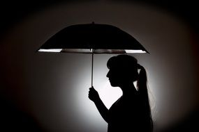 silhouette of a woman under umbrella
