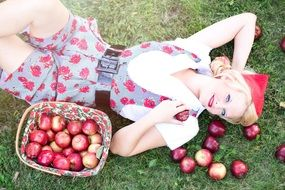 girl in a red cap is lying on a lawn with red apples