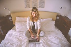 Blonde woman working in bed laptop typing