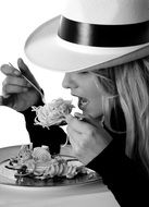 pretty blonde girl in hat eating pasta