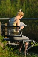 woman on a bench reading a newspaper