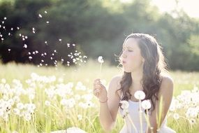 girl blows dandelion seeds