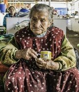 old woman with a cup of coffee in Peru