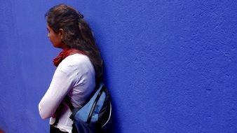 photo of a girl on a background of blue wall