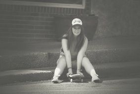 Happy girl in baseball cap with skateboard