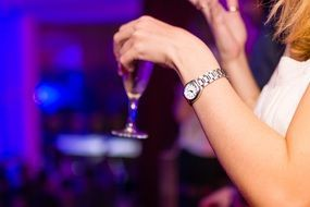 Woman hand holding glasses with drink party club night