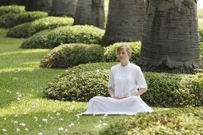 girl in a white suit meditates in a park at Wat Phra Dhammakaya