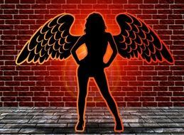 silhouette of a woman angel on a background of a brick wall