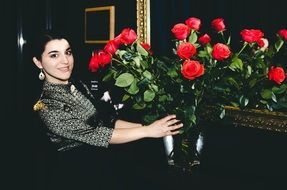 girl and a bouquet of red roses in a vase