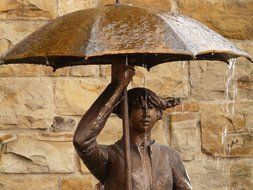Bronze statue of the woman holding umbrella