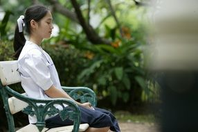 Asian girl meditating on bench in park