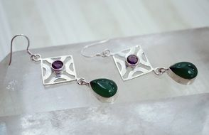 two earrings with green stones