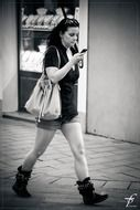 black and white photo of a girl walking down the street with a phone in her hand