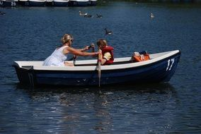 a woman with a child in a rowing boat on the lake