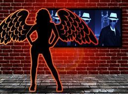 silhouette of a woman with wings on the screen background on a brick wall