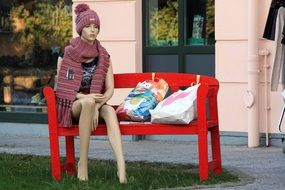 girl mannequin on a red bench