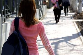 girl in a pink sweater and backpack