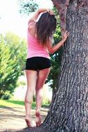 girl in a pink tank top and black shorts against a tree