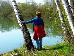 woman near birch by the lake on a sunny day